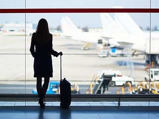 Silhouette of woman with suitcase at the airport