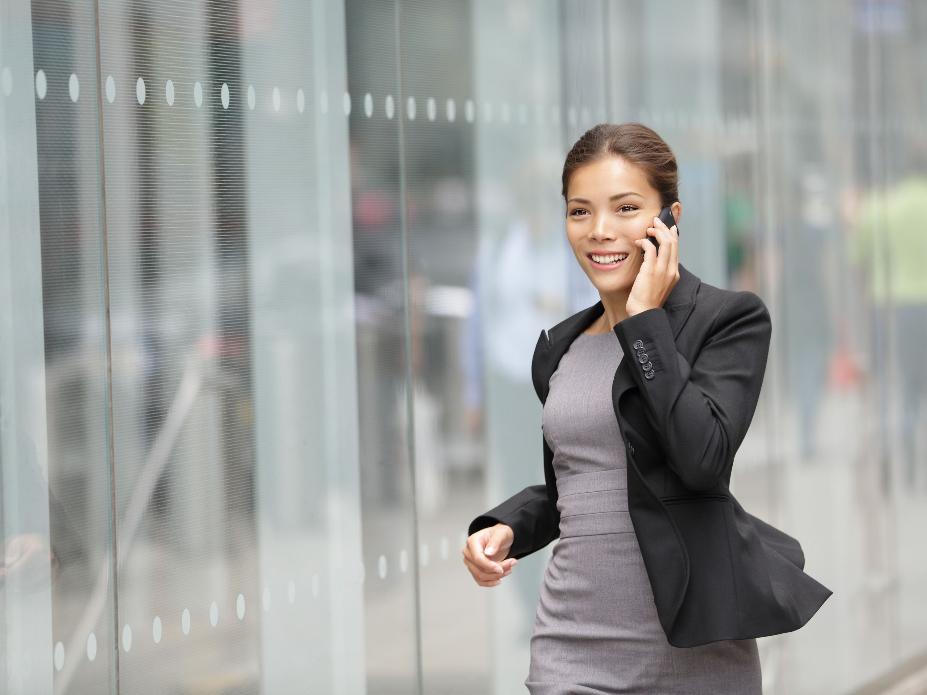 Phoning woman infront of glass facade